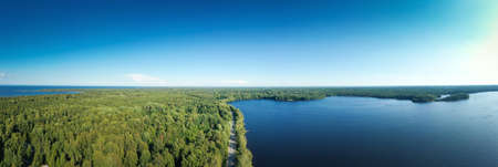 Asphalt freeway through summer forest near lake. Panorama aerial view from drone Reklamní fotografie