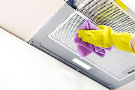 Cleaning the house. Washing kitchen hood, hand in glove clean aluminum filters. Clear extractor without fat. Stock Photo