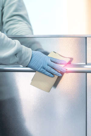 Cleaning and sanitizing an elevator push button control panel against bacteria and virus. Infection prevention and control at public places during epidemic. Covid-19 second wave concept