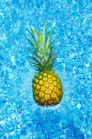 Pineapple falling into water with splashes in swim pool at sunny day. Tropical summer vacation concept card.