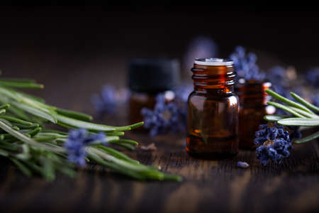 Rosemary and lavender essential oils in dark glass bottles on wooden background, herbal and floral sprigs with amber jars. 스톡 콘텐츠