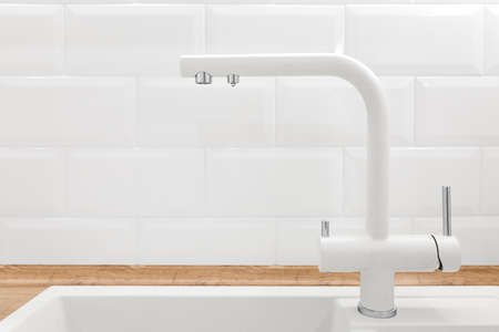 Faucet in white kitchen interior with tiled wall and wooden countertop, nobody
