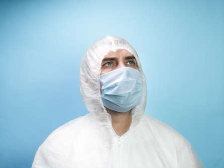 Man in medical mask wearing protective uniform on blue background. Covid 19 pandemic concept 스톡 콘텐츠