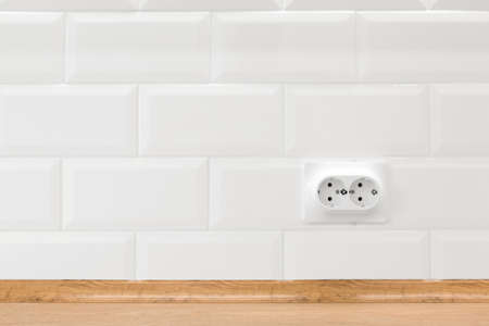 Socket in white kitchen interior with tiled wall and wooden countertop, nobody 스톡 콘텐츠