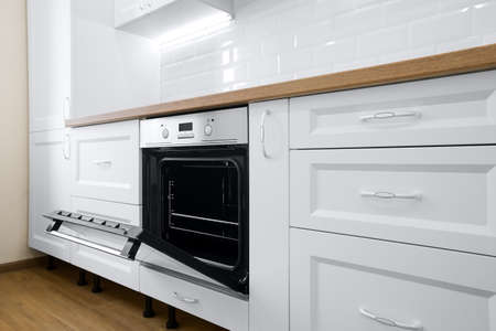 Modern cooking stove in white kitchen interior with tiled wall and wooden countertop, nobody