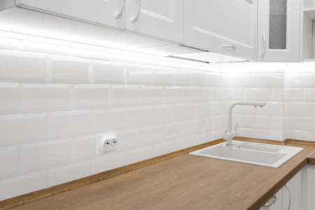 White kitchen interior with tiled wall and wooden countertop, nobody 스톡 콘텐츠