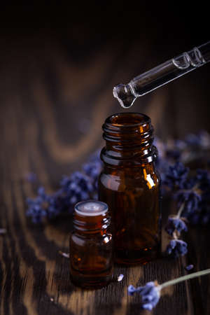 Dripping Lavender essential oil from pipette into glass bottle on dark wooden background with blurred flowers. Aromatherapy concept