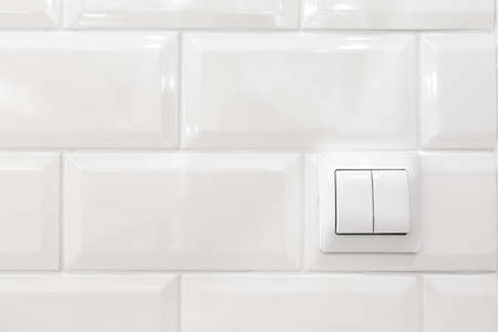 Switch buttons in white kitchen interior with tiled wall, nobody