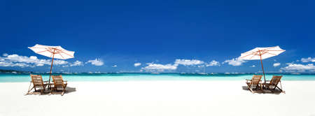 Sun umbrellas and wooden beds on tropical beach. Caribbean vacation on tropical shore. Long banner 스톡 콘텐츠