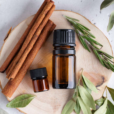 Natural ingredients for immunity boosting, aromatherapy with essential oils of rosemary, cinnamon and eucalyptus plants. Herbs and amber bottles top view. 스톡 콘텐츠