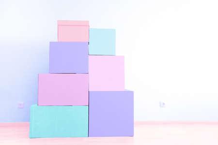 Stack of cardboard boxes for moving in interior apartment, movement. Pink and lavender pastel colors toning. No people in empty room