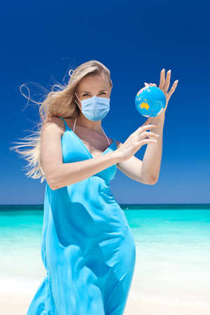 Woman in medical mask holding a globe in hands on beach. World lockdown. Travel isolation 스톡 콘텐츠