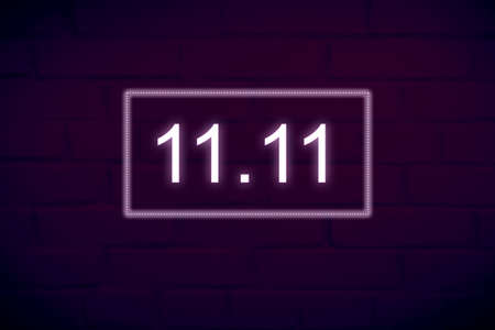 Dark brick wall background with neon electric inscription date 11.11 - Single Day and Shopping Season Concept. 스톡 콘텐츠