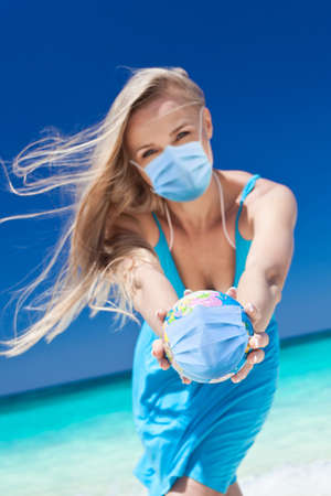 Woman wearing medical mask holding a globe with mask in hands on beach. World lockdown. Travel isolation. Focus on globus
