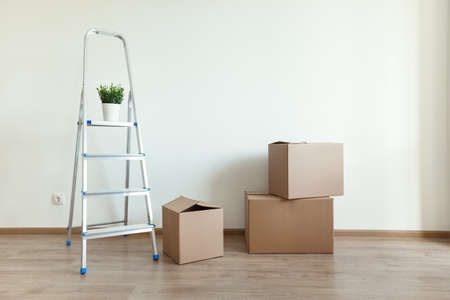 Movement objects and relocation concept. Carton boxes and ladder in new house, closeup