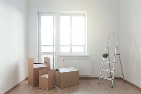 Cardboard boxes on wooden floor in empty room with window against sun light. Movement to new apartment. Nobody 스톡 콘텐츠