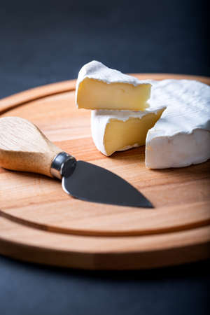 Sliced camembert on cheese platter with knife on dark background. Top view