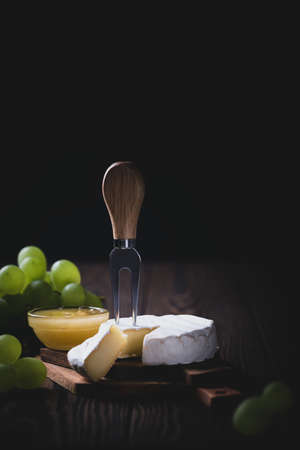 Sliced Camembert with fork on wooden cheese platter on dark background, card for menu