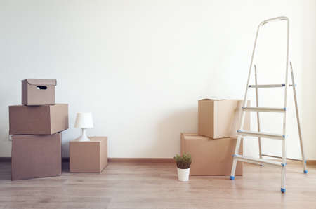 Different cardboard boxes for moving and ladder at room interior movement or delivery concept, empty wall with copy space for your text