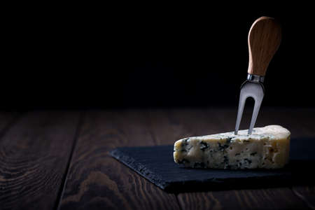 Piece of blue cheese woth fork on slatter on dark wooden background, copy space