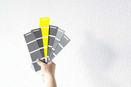 What color in 2021 will you choose? Trendy colors on palette - IIluminating Yellow and Ultimate Gray. Holding color swatch guide in hand