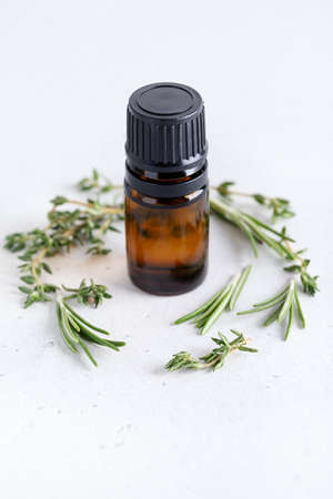 Bottle with essential oil on neutral background with herbal plants. Rosemary and thyme sprigs with dark glass jar. Natural cosmetics or aromatherapy concept