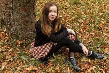 Beautiful romantic girl in a park autumn scenery looking at the camera, sitting down next to a tree, enjoying the perfect weather in a sunny day. Gorgeous young woman outdoors. Full length body shot Stock Photo