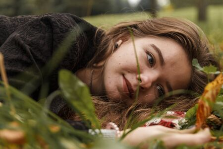 The girl lies on the ground in the leaves and looks at the camera
