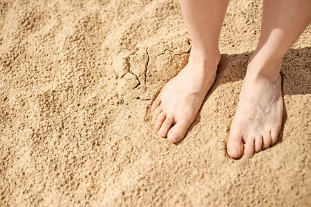Bare feet are on sand