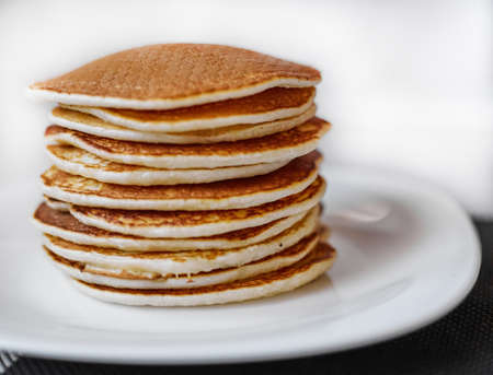 A stack of pancakes is on a white plate, Pancakes on a white plate top view, Pancakes on a white plate,