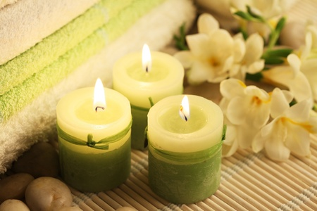 candles towels and freesias on wooden carpet photo