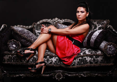 beautiful brunette in red dress on sofa Stock Photo - 8511882
