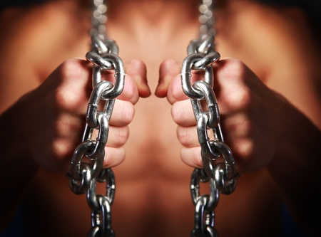 athletic young man with chains on his fists photo