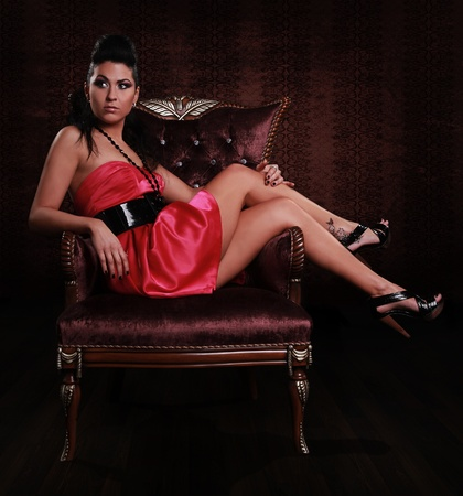 lounging: young beautiful model on classic fashionable chair Stock Photo