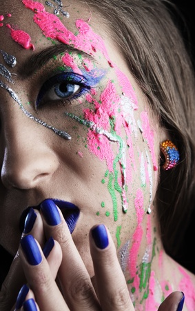 close-up of woman with colored paint on face photo