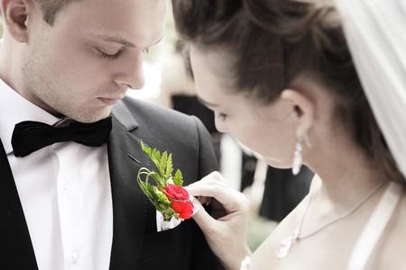 신랑의 재킷에 꽃을 조정하는 신부