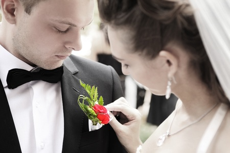 bride adjusting flower on grooms jacket photo