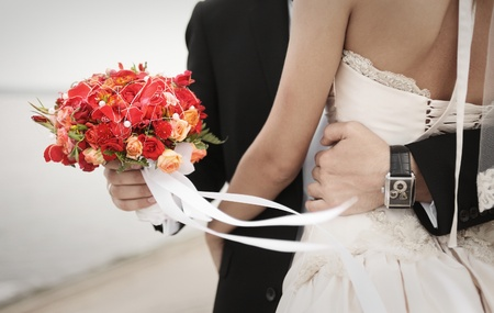 groom with bouquet embracing bride Stock Photo - 8679627