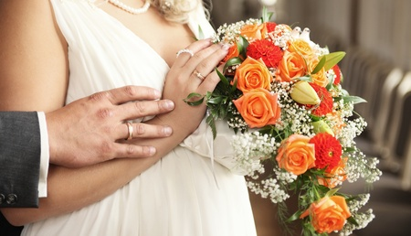 hands with rings and bouquet photo