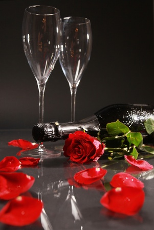 a bottle of dry champagne, glasses and red rose photo