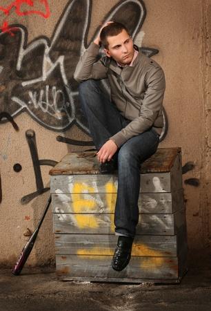 모래 상자 ner에 앉아있는 젊은 남자 벽을 그렸습니다.