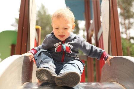 little kid getting ready to slide Standard-Bild