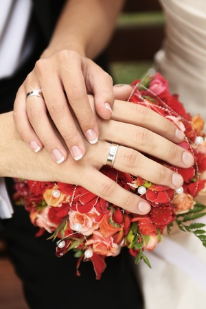 newly wedded couple: hands of newly wedded couple with shiny rings on bouquet