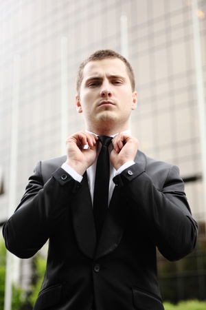 young businessman adjusting his tie photo