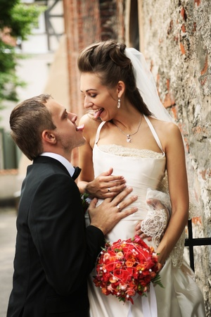 newly weds showing tongues to each other photo