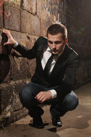 stylish handsome man sitting in dark tunnel photo