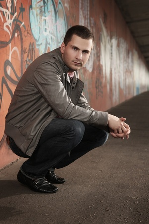 shaved: portrait of young stylish man sitting in tunnel