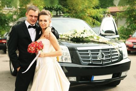 newly wedded standing near wedding car