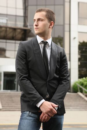 young stylish businessman against office building photo