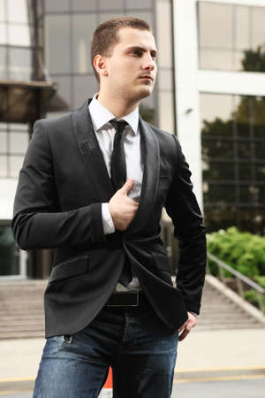 young stylish businessman near office building photo